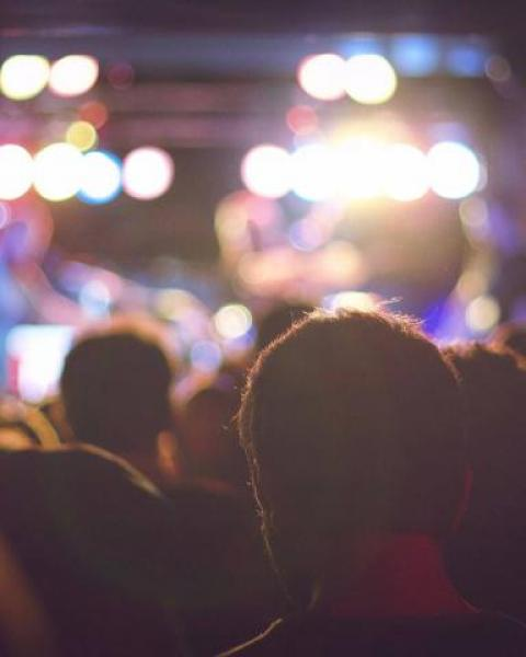 Crowd of people in a music venue bathed in bright colorful lights with musicians on stage