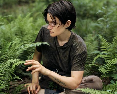 Adrianne Lenker sitting in the forest