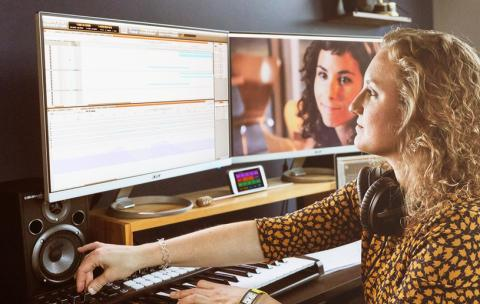 Woman composing to picture with her DAW and MIDI controller.