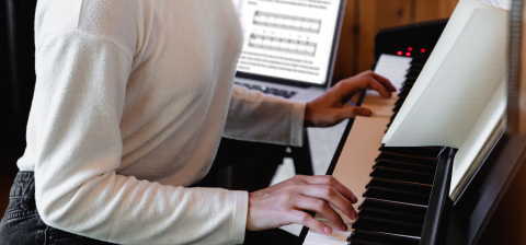 Girl playing the piano with a computer in the background