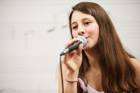 Girl singing into a microphone.