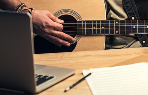 hand on guitar near computer
