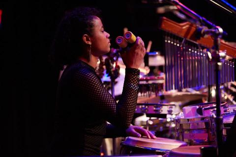 Woman playing percussion in a ensemble.