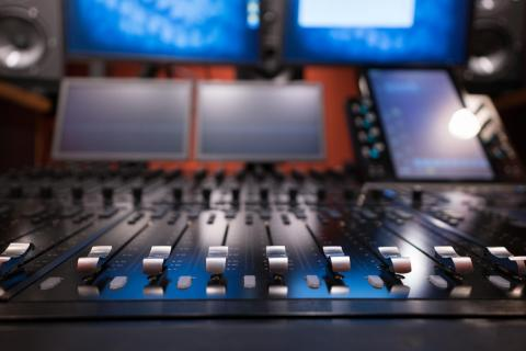 A digital recording console with monitors and multiple screens.